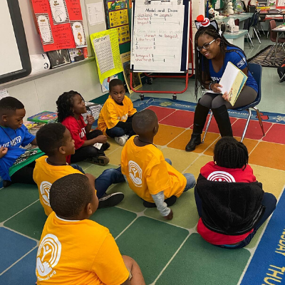 A Women United volunteer reads to students