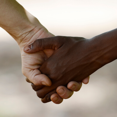 White and black hands holding each other